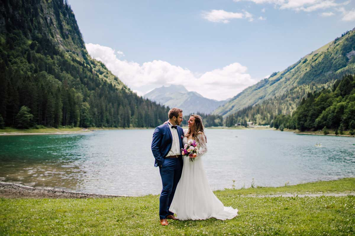 married bride and groom posing in lake montriond at the french alps