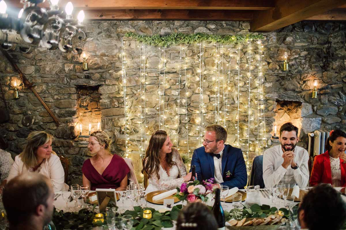 wedding couple having diner in a long table at the farmhouse venue