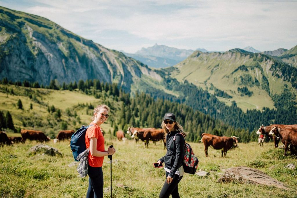 ladies take in the moutain views and cows whilst doing an easy hike inn morzine