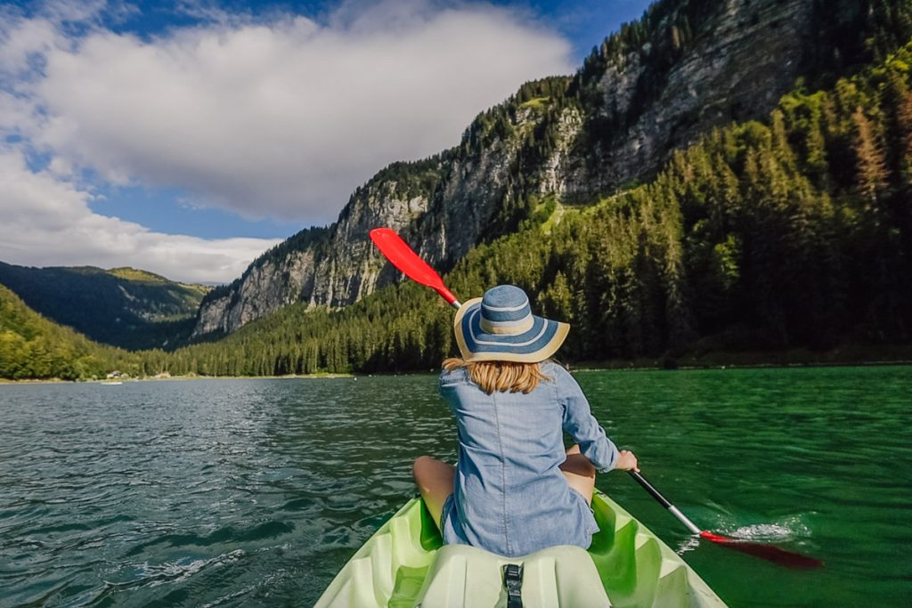 lady in summer hat kayaks on lake montriond in morzine