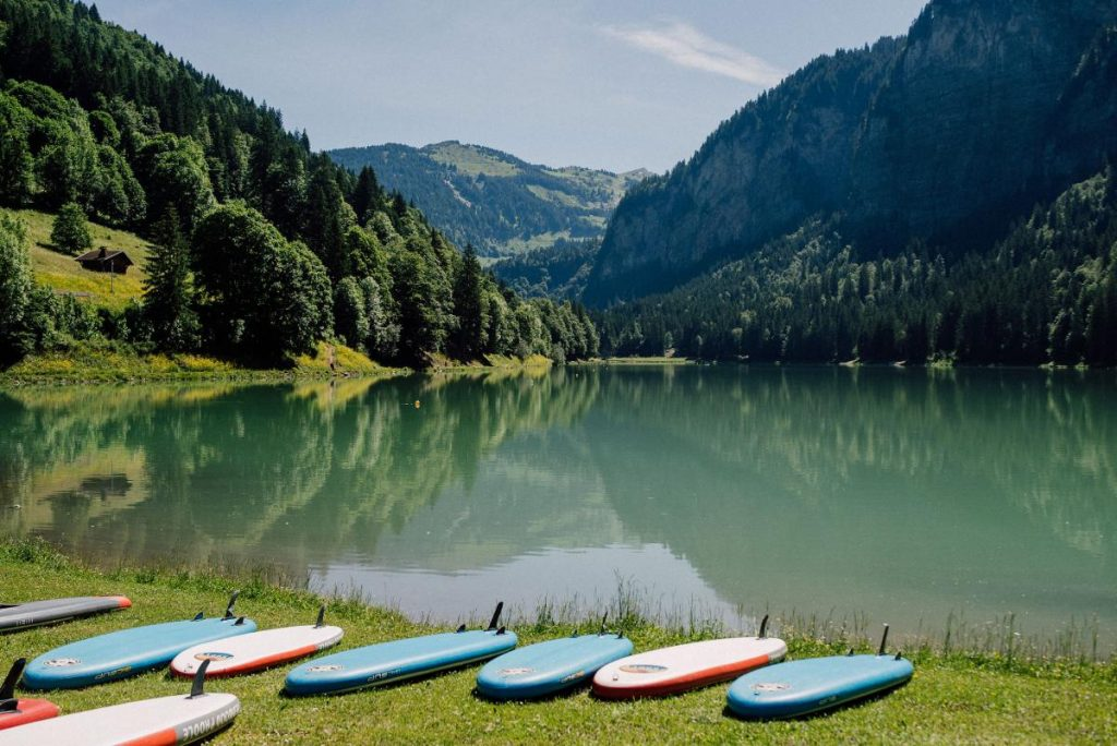 paddle boards on the shore of lake montriond, a beautiful alpine lake in morzine