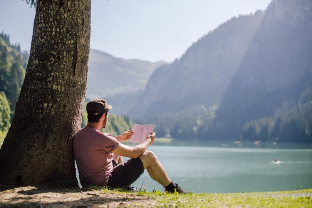 man reads a book under a tree at lake Montriond in Morzine