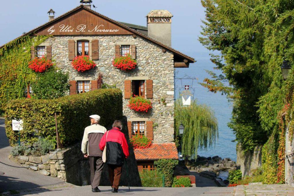 couple walk around a lakeside town near Morzine