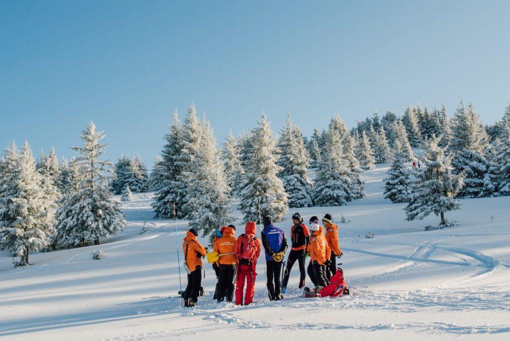 secours en montagne team discuss a rescue during training