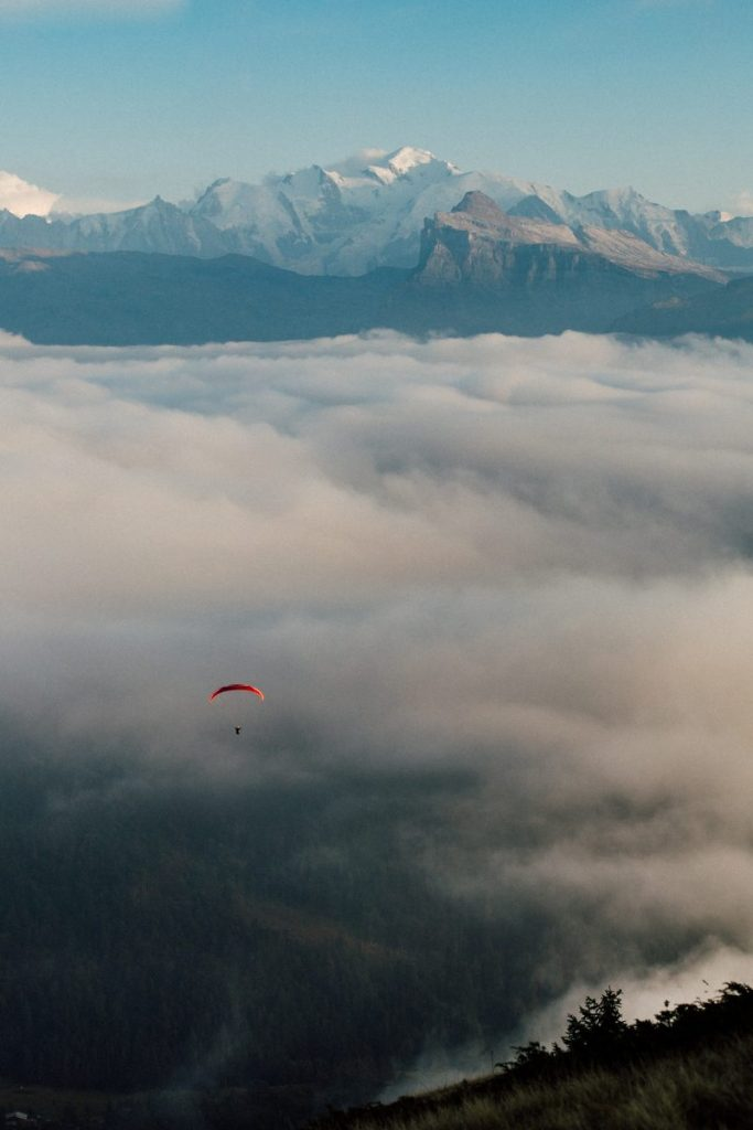 paraglider flying above clouds with mont blanc in the horizon