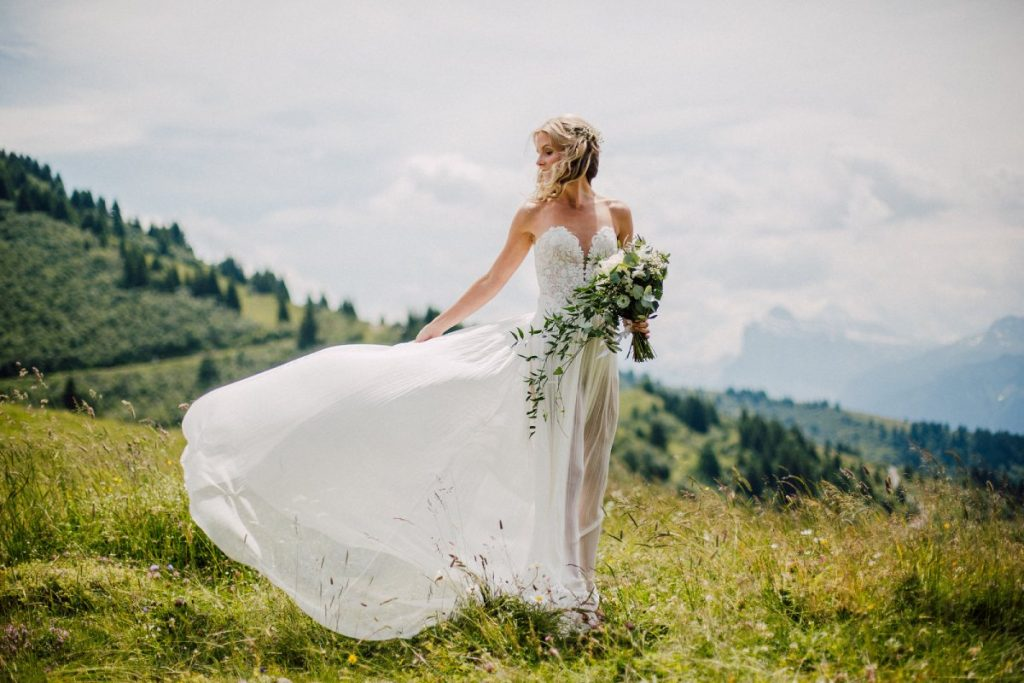 Beautiful bride poses on mountain top after finding perfect wedding venue in the French Alps