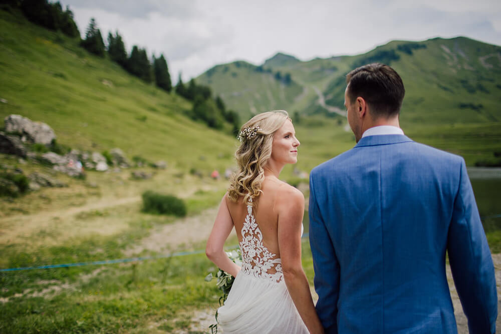 Couple pose at alpine lake before perfect wedding in the Frech Alps