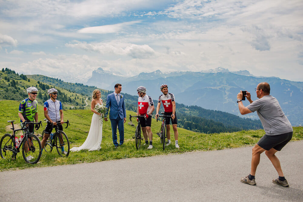 Newly weds pose for photo with cyclists atop an Alpine mountain pass