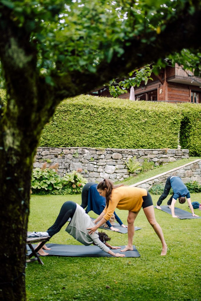 yoga teacher on a retreat helping a student with downward facing dog