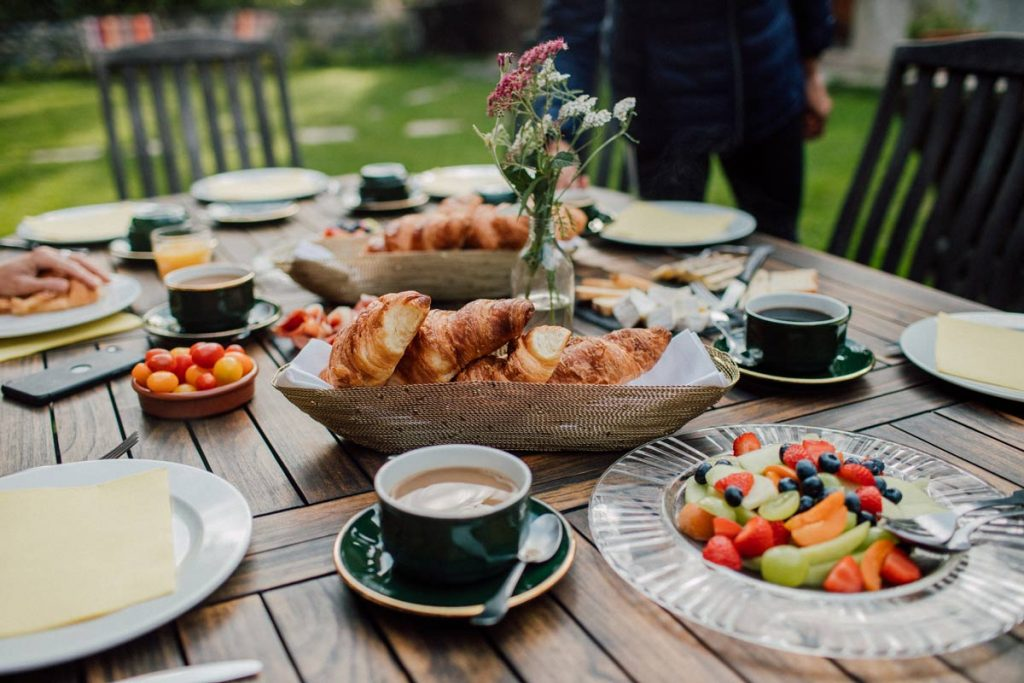 breakfast table with coffee, fruits and croissants during a yoga retreat