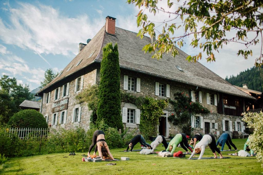 A group of people doing yoga in the garden of a hotel in Morzine